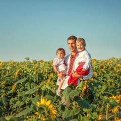A father and two children in Ukrainian costume at sunset in a fi