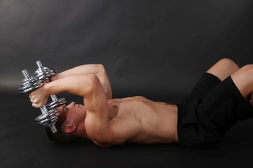 Handsome young muscular sportsman execute exercise with
