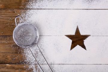 Star figure made of sugar powder on wooden background