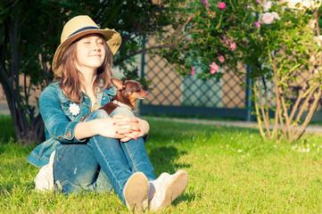 Smiling girl having sunbath with small dog. Summertime enjoyment