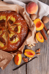 Delicious cake with peach and nuts on wooden table close up