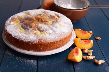 Delicious cake with peach and nuts on wooden table