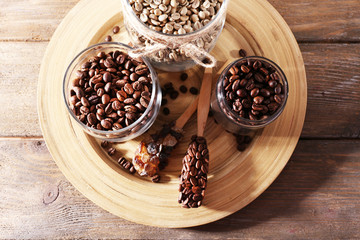 Coffee beans in jars on bamboo plate on wooden background