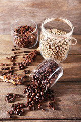 Glass jars and spoon with coffee beans on wooden background