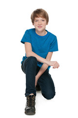 Preteen boy sits on the white background