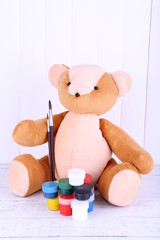 Toy bear and paints on wooden wall background