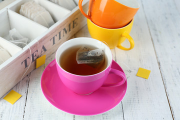 Cup with tea and tea bags on wooden table close-up