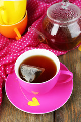 Cup of tea, teapot and tea bags on wooden table close-up