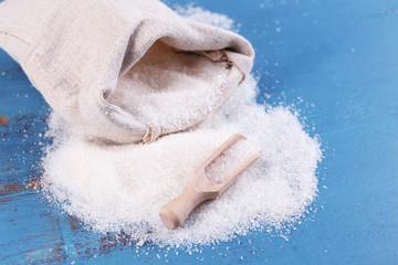 Sugar in bag on color wooden background
