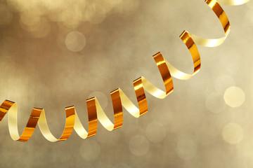 Serpentine ribbon on golden shiny background