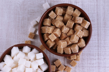 Brown and white refined sugar in color bowls
