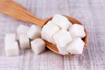 White refined sugar in wooden spoon on wooden background