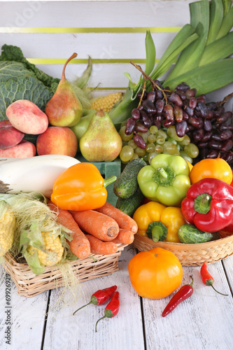 canvas print picture Vegetables in baskets on white wooden box background