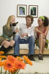Drei junge Leute sitzen auf dem Sofa