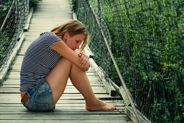 Портрет задумчивой одинокой девушки на мосту