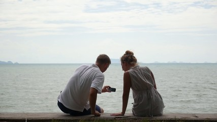 Attractive Teenage Couple Using Cellphones near the Sea.