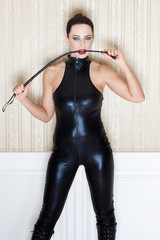 Sexy woman in latex catsuit bite whip