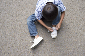 Boy connecting the string of athletic shoes
