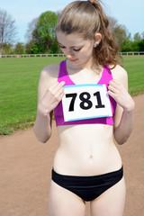 Leichtathletin befestigt Startnummer an Sport-Top