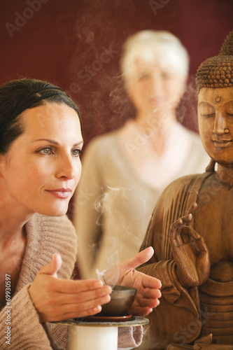 canvas print picture Frau mit Buddha-Statue und Schale mit Räucherstäbchen
