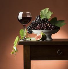 Red wineGlass  on the wooden table with grapes