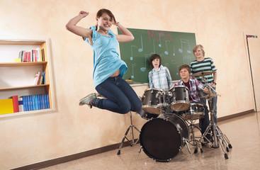 Girl -Springen mit Jungen im Hintergrund spielt Schlagzeug