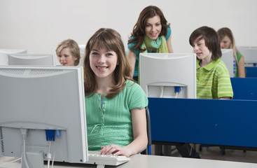 Girl lächelnd mit Lehrer erklärt den Schülern im Hintergrund
