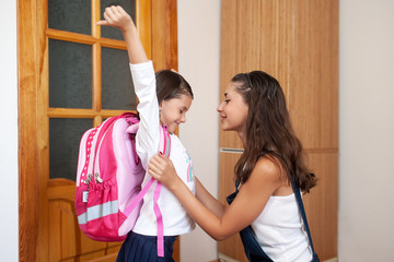 mother helping her daughter get ready for school