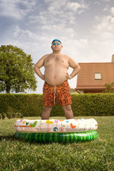 Funny overweight man about to swim in the back yard pool