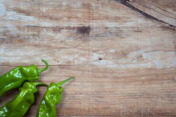 Some green pepers in old wooden background