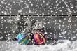 canvas print picture - Bunte Weihnachtskugeln auf Schneehaufen, Holzwand als Hitergrund