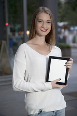 young woman with a tablet on the street