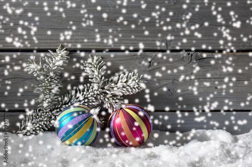 canvas print picture Bunte Weihnachtskugeln auf Schneehaufen, Holzwand als Hitergrund