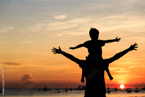 father and son on sunset beach - 69936702