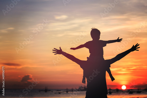 father and son on sunset beach - 69936771