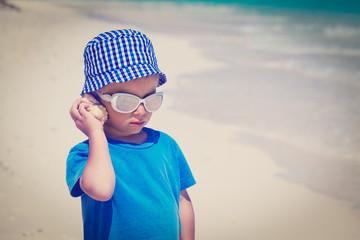 little boy listening seashell at the beach