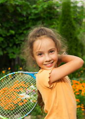 portrait of smiling little girl playing tennis in summer