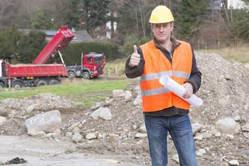 Projekt manager steht auf Baustelle zeigt Daumen hoch