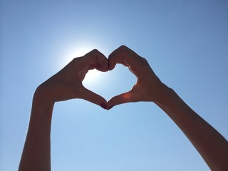 hands show heart shape on sun and blue sky background
