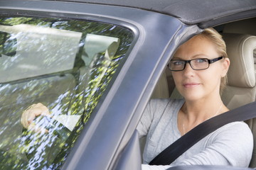 Woman wearing glasses, smiling, driving a car