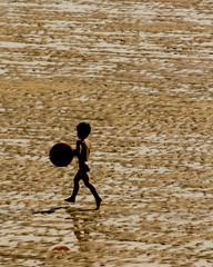 Niño jugando con balón en la playa