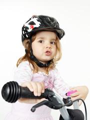 Cute girl with bicycle helmet on a bike