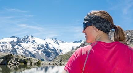 Young woman watching a mountain lake
