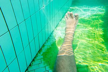 Man at the swimming pool,  underwater photo of legs