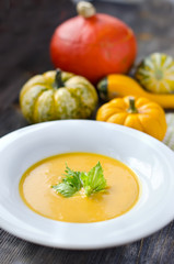 Pumpkin soup in a plate with pumpkins