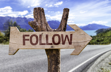 Follow wooden sign with a road background
