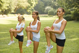 Fotoroleta Fitness class. Beautiful young women doing exercise at summer pa