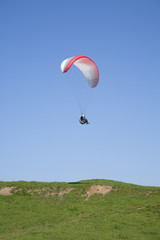 paraglider flying over green field