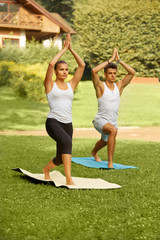 Yoga Exercise. Young couple meditating  in fitness club