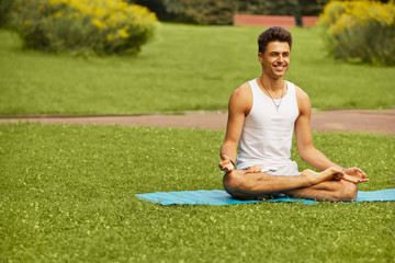 Yoga Exercise. Portrait of athletic man doing a yoga at summer p